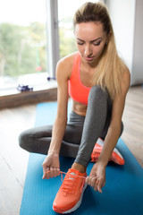 Woman sitting on mat and tying shoelaces in a fitness club