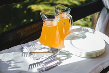 Orange juice in glass jugs on table in self service restaurant. Refreshing cold drinks for hot sunny summer weather. in natural lighting of sun. Horizontal color image.