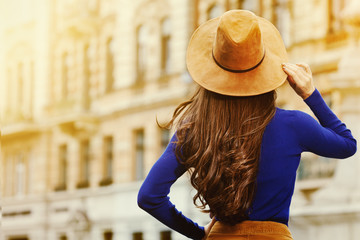 Female fashion concept. Outdoor portrait of young beautiful fashionable lady walking on the street. Model wearing stylish hat and clothes. Sunny day. Back view. Waist up. Copy space for text Wall mural