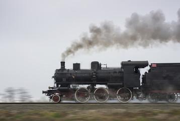 Old steam locomotive running on rails