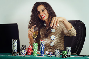 Happy young woman playing poker online via laptop , winning