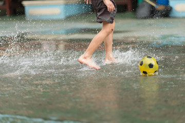 Little boy kicking ball in the water logging on the street
