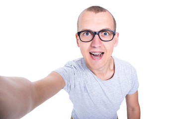 funny young man in glasses with braces on teeth taking selfie ph