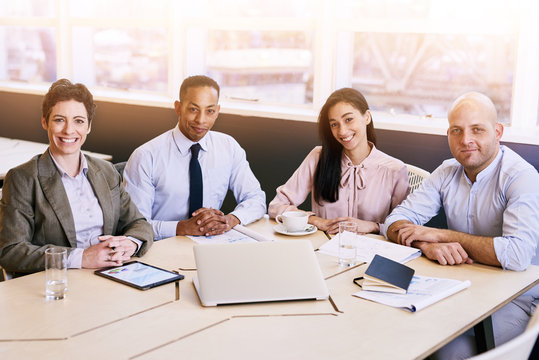 4 business professionals all looking at the camera during a business meeting in a modern conference room with a large window behind them with bright natural light coming in.