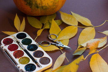 watercolor paints, pumpkin, yellow leaves on a brown background
