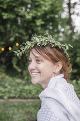 Smiling woman with a flower wreath in her hair sitting in a garden.