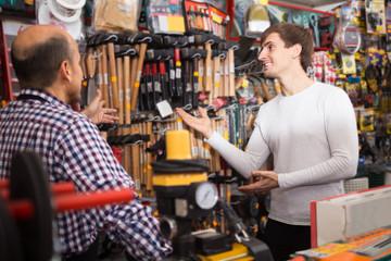 Salesman showing different hammer in supermarket