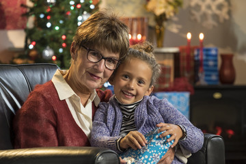 Little girl holding her Christmas present on grandmother's lap