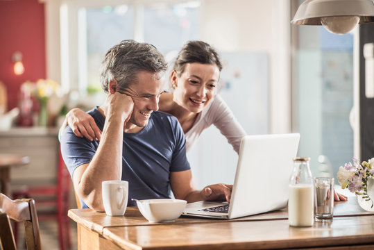 A couple using a laptop while having breakfast in the kitchen