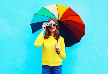 Happy smiling young woman with vintage camera holding colorful u