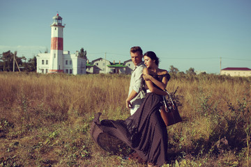 young couple hipster indie style in love walking in countryside, holding hands, lighthouse on background, warm summer day, sunny, bohemian outfit, vintage bag with flowers