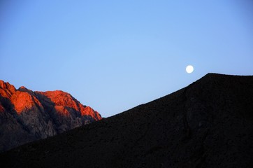 Bright moon in the blue sky behind hills in Pisco Elqui in Chile, South America