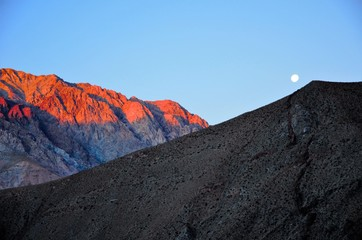 Bright moon in the blue sky behind hills with the little village Pisco Elqui in the foreground in Chile, South America