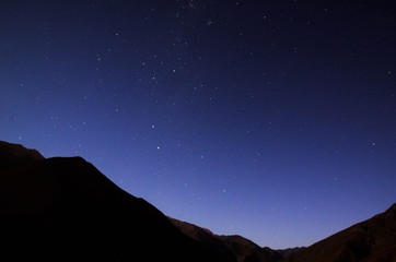 Stargazing in Elqui Valley with hundreds of stars in the sky between black hills in Chile, South America