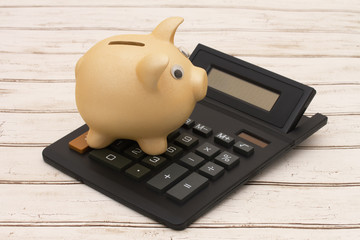 A golden piggy bank and calculator on wood background