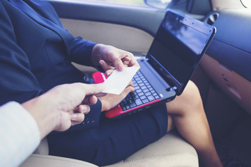 Business woman handing a business card in the car.She showing an