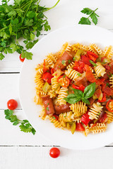 Pasta with tomato sauce with sausage, tomatoes, green basil decorated in white plate on a wooden background. Top view