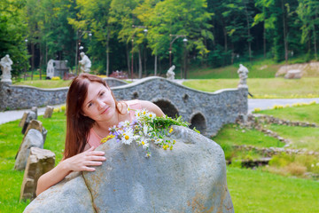 beautiful woman with flowers walks in the park