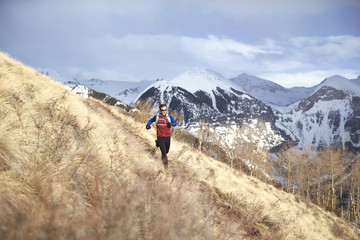 An adult male trail running in the mountains of Telluride Colorado.