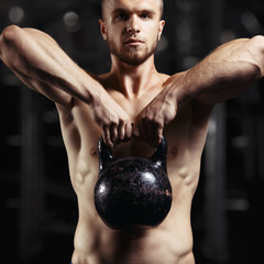 Fitness man doing a weight training by lifting heavy kettlebell