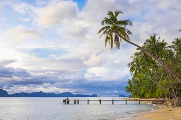 Pier and palmtrees on Dolarog Beach, El Nido, Philippines