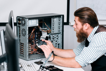 Repairman disassembling computer unit for repair. Bearded man taking electronic component out of CPU. Renovation, fix, construction concept