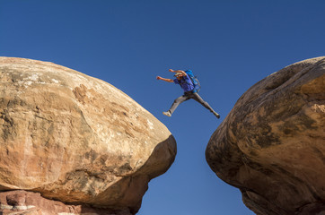 A man jumping between two rocks, Needles District of Canyonlands National Park, Monticello, Utah.