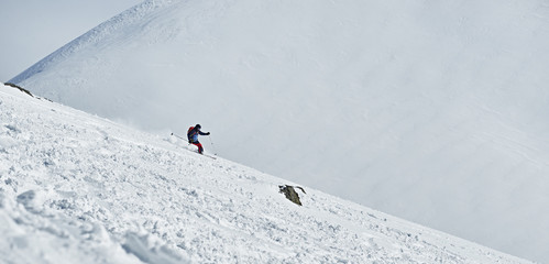 Man skier slides down the mountainside