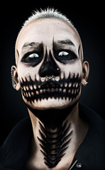 Portrait of a scary fierce staring male with skull makeup and piercings on a black background. 3d rendering
