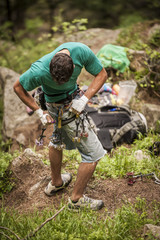 Italian climber attaching some climbing gear (friends and nuts) to his harness while preparing for climb an hard crack route. Esigo, Italy.