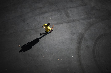 A male runner and his shadow.