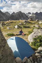 A woman camping in Titcomb Basin, WInd River Range, Pinedale, Wyoming.