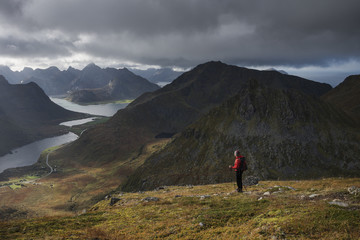 Female hiker on trail towards summit of Stornappstind (740m), Flakstadøy, Lofoten Islands, Norway