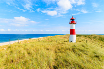 Fototapete - Ellenbogen lighthouse on sand dune against blue sky with white clouds on northern coast of Sylt island, Germany