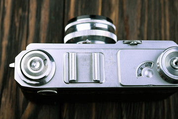 The old film camera on wooden table.