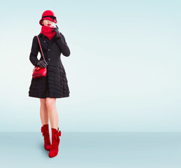 Winter fashion woman with red hat,scarf,handbag purse,boots, wearing black coat and gloves isolated on light blue background. copy space.