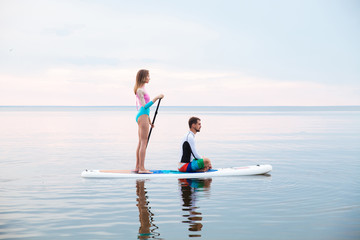 Young couple paddling on sup board
