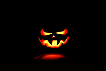 very scary Halloween pumpkin isolated on black background with i