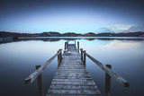 Wooden pier or jetty on a blue lake sunset and sky reflection on