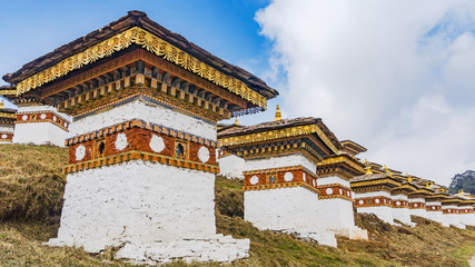 Wall Mural - Dochula pass 108 chortens (Asian stupas) is the memorial in honour of the Bhutanese soldiers in the Timpu city with the grass landscape and cloudy sky background, Bhutan