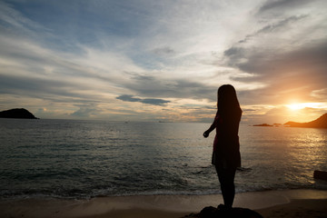 Woman silhouette on the beach at sunrise