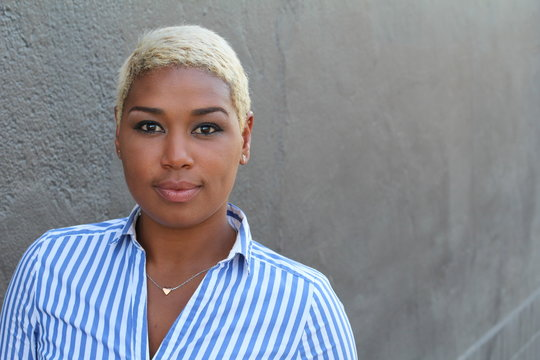 Beautiful young African American woman with short dyed blond hair looking at camera with a relaxed neutral expression