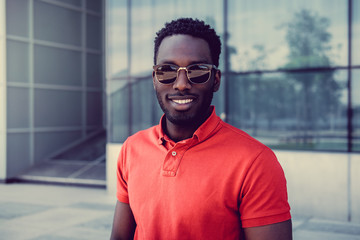 Smiling African American male in sunglasses.