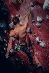A man climbing on a red indoor climbing wall.