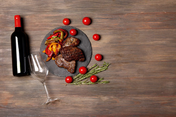 Delicious steak with red wine on wooden background