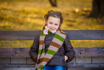 little girl sitting on the banch autumn portrait