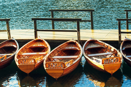 Small wooden boats docked and tied to empty pier