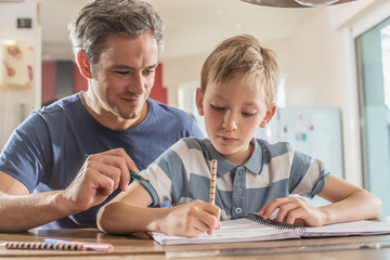 Young boy doing his school homework with his father, at home