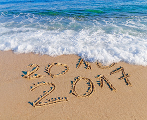 Happy New Year 2017 replace 2016 concept on the sea beach