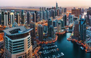 Fantastic view over illuminated architecture of a big city at night. Dubai Marina, United Arab Emirates. Scenic travel background.